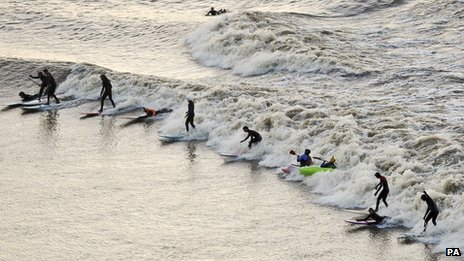 Surfers, kayakers and wave-skiers ride the tidal Severn Bore as it passes Newnham, Gloucestershire on 2 February
