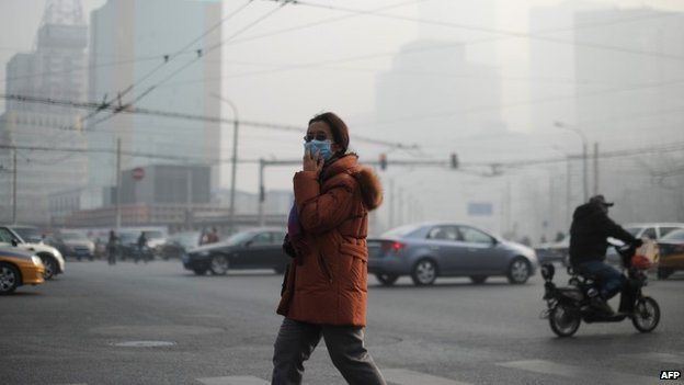 A woman wearing a face mask makes her way along a street in Beijing on January 16, 2014.
