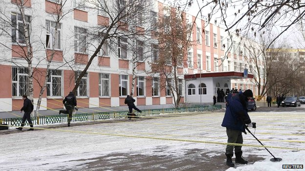 A security service member uses a mine and metal detector as he works near the building of a high school, where a shooting incident has occurred, on the outskirts of Moscow