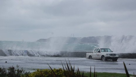 Waves crashing over wall onto car