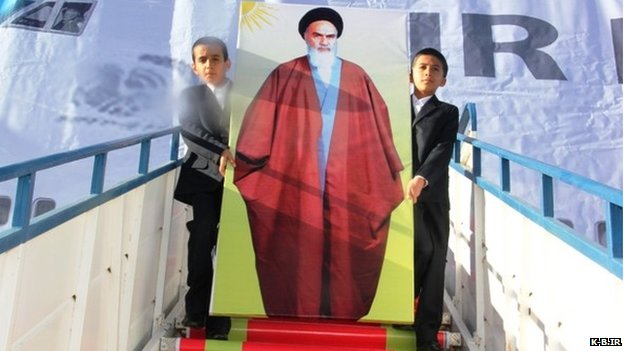 Khomeini's likeness in front of a painted backdrop of an Air France jet