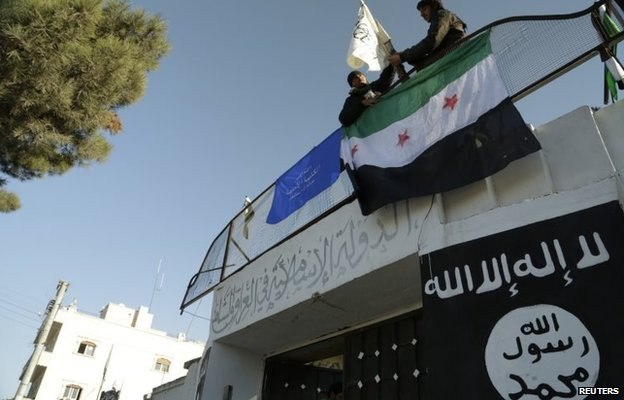 Syrian rebel fighters fly the opposition flag at the entrance to a captured ISIS base in Aleppo (9 January 2014)