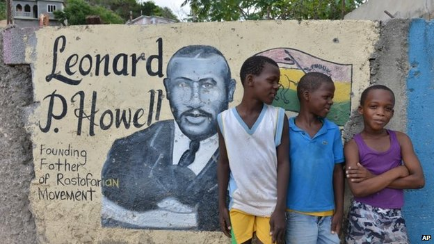 Boys pose in front of a mural of Leonard P Howell at The Pinnacle