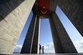 People pass under a memorial for Turkish soldiers at Cape Helles near Canakkale