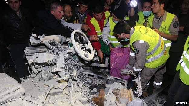 Lebanese emergency personnel inspect the wreckage of a minibus at the site of an explosion on 3 February 2014 in Choueifat, south of the capital Beirut.