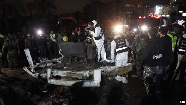Lebanese police forensic experts inspect the wreckage of a minibus at the site of an explosion on 3 February 2014 in Choueifat, south of the capital Beirut.