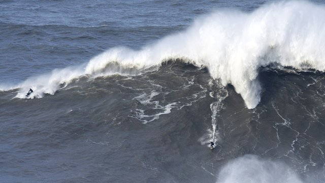 Andrew Cotton riding an enormous wave