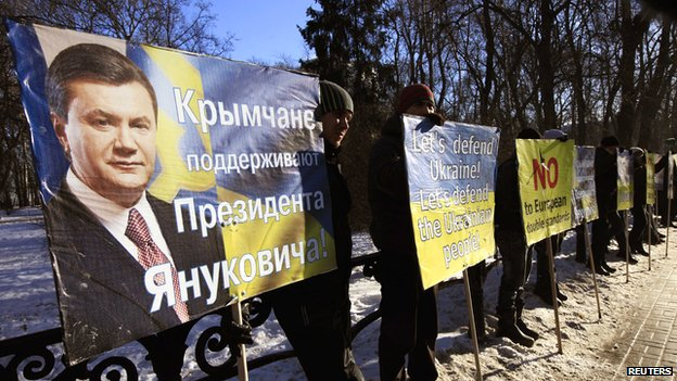 Supporters of Ukrainian President Viktor Yanukovych hold placards during a protest outside the Parliament in Kiev