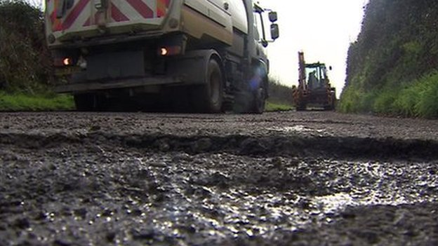 Roadworks truck approaches large pothole
