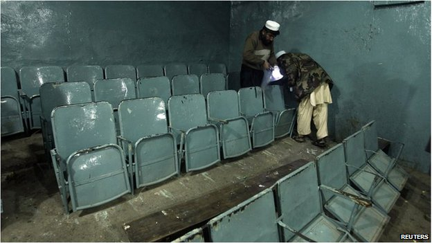 Security officials collect evidence following a bomb attack at a cinema in the Pakistani city of Peshawar on 2 February 2014.