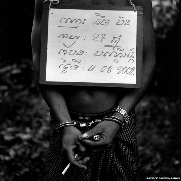 A handcuffed poacher is photographed with a notice bearing details of his name, age and the nature and date of his crime