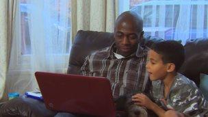 Basil shows seven-year-old son Jaeden a website