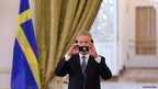 Swedish Foreign Minister Carl Bildt takes pictures on his phone