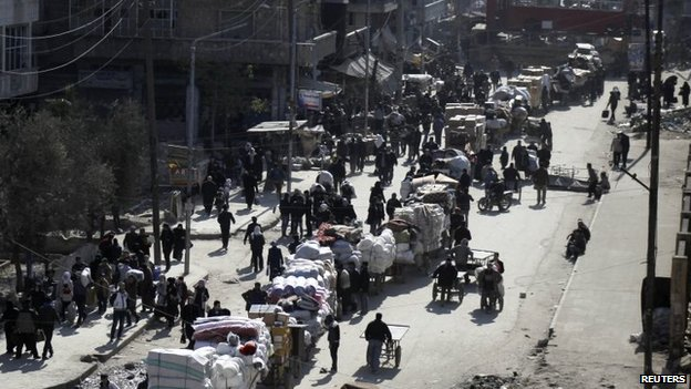 A street packed with Aleppo residents carrying large packs as they flee the barrel bombs (4 February 2014)