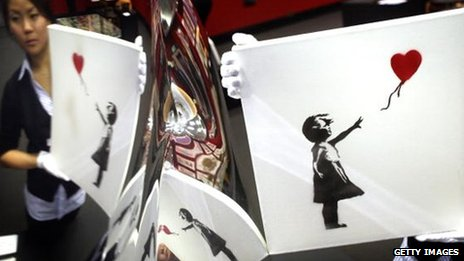 'Balloon Girl' 2003 by artist Banksy is held by Bonham's Andrea Lee and is reflected in a mirror polished vase