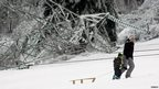 A woman and child walk past a fallen pylon with a sledge.