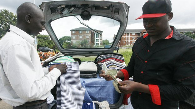 A clothes trader in Harare, Zimbabwe's capital, counting money by his car