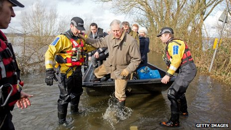Prince Charles gets out of a boat on a flooded road