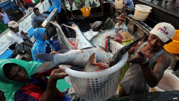 File photo: workers unloading fish from a boat at a jetty near a fish market in Yangon, Burma, 11 September 2013