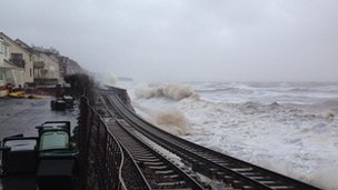 Rail tracks suspended in the air as waves batter the sea wall in Dawlish