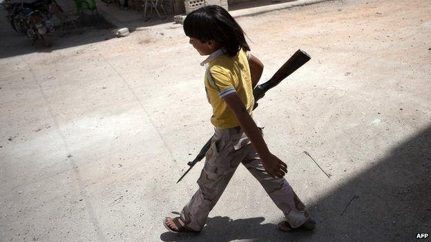 A young Syrian boy holds a rifle in the town of Maarat al-Numan (13 June 2013)