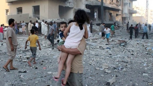 A man carries two children away from the scene of an explosion in the northern Syrian city of Raqqa (7 August 2013)