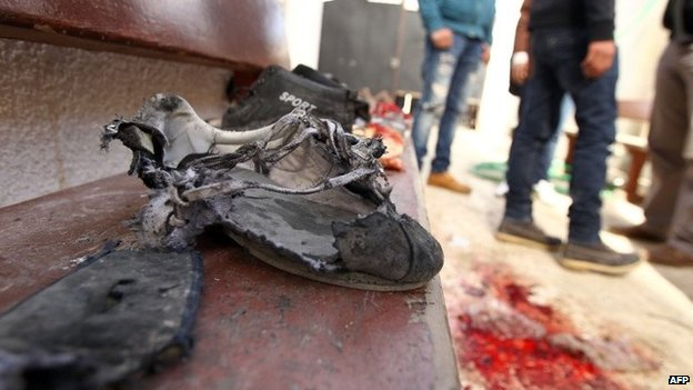 Libyan youths stand next to blood stains and torn shoes at the scene of a blast at a primary school in the Libyan city of Benghazi - 5 February 2014