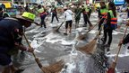 City workers and anti-government protesters clean a street in Bangkok