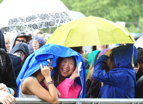 Members of the crowd during the rain at the Barclaycard Wireless Festival 2012 at Hyde Park in London.