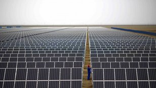 A worker inspects solar panels at a solar farm in Dunhuang, 950km (590 miles) northwest of Lanzhou, Gansu Province, Chuina