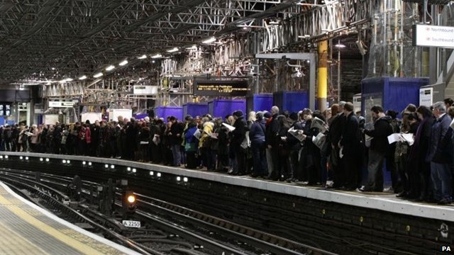 Commuters waiting for a train on a platform at Farringdon Underground station