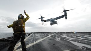 An Airman directs a V-22 Osprey as it lifts off