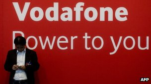 Vodafone sign and a man texting