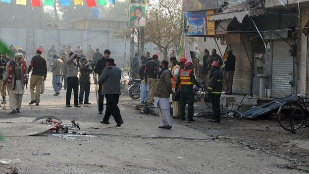 Pakistani security officials inspect the site of a bomb attack in Rawalpindi on 20 January