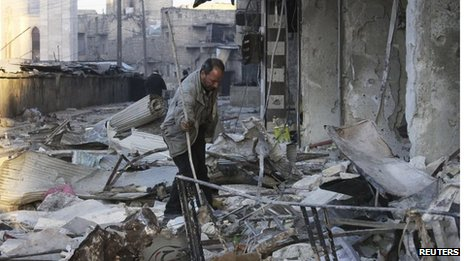 A resident searches through rubble at a site hit by what activists said was a barrel bomb dropped by the Syrian military during a previous attack