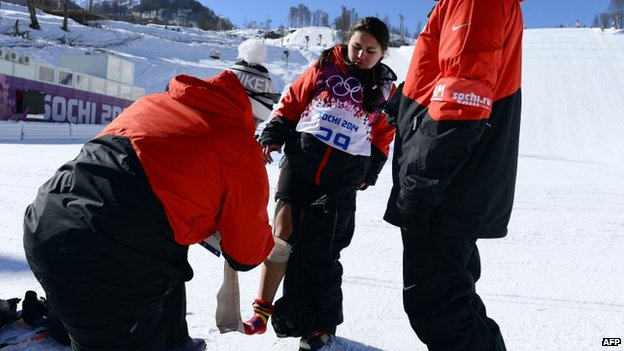 A trainer wraps a bandage around with Julia Marinos' leg during a training session at the Rosa Khutor Extreme Park on 5 February, 2014