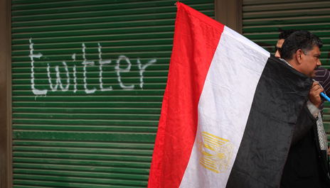 "Protester with Egyptian flag by ""twitter"" graffiti, Tahrir Square 2011"