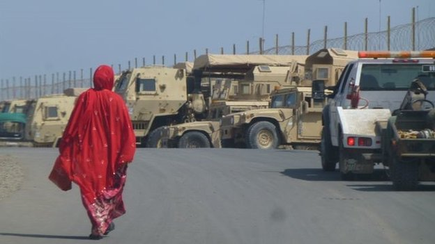 Woman in bright red robes walks past military vehicles in Djibouti