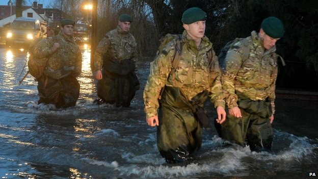 Members of 40 Commando Royal Marines wade through floodwater in Moorland
