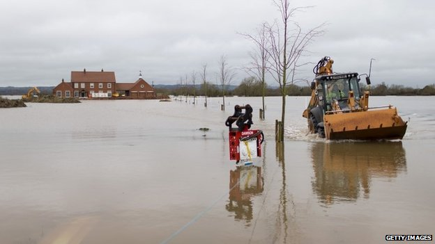 A mechanical digger is driven through floodwater in the village of Moorland