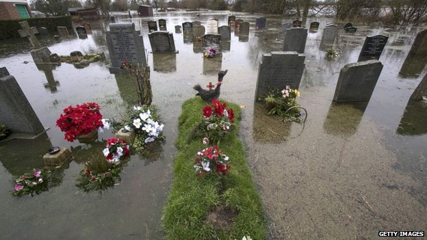 Rising floodwaters inundate the graveyard of Moorland church