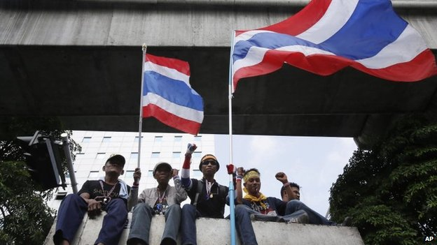 Anti-government protesters wave Thai national flags as they ride on the roof of a truck parading through central Bangkok, Thailand, on 7 February 2014