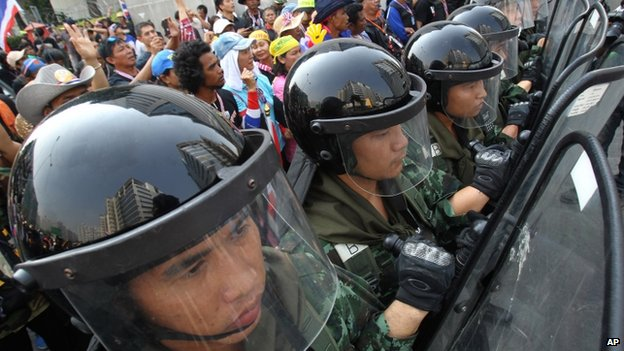 Thai soldiers stand guard to block anti-government protesters, left, during a rally outside the office of the permanent secretary for defence where Prime Minister Yingluck Shinawatra was reportedly working on 3 February 2014