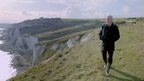 Jeremy Paxman walking on cliff top