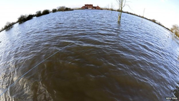 A property is seen completely surrounded by flood water in the village of Moorland in south west