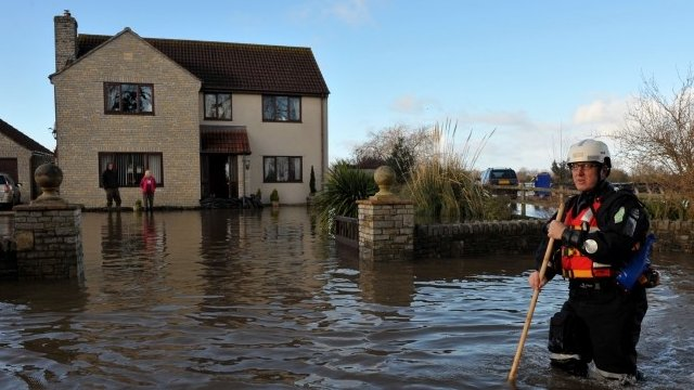 An emergency worker walks down the road outside a property in Moorland, Somerset