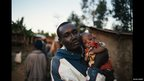 A man holding his baby daughter in a village in western Kenya