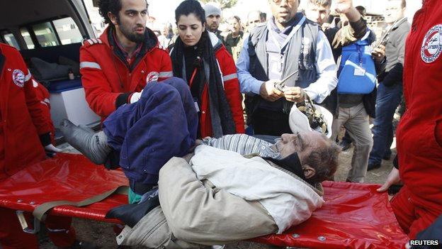 Members of the Syrian Arab Red Crescent assist a wounded man evacuated from a besieged area of Homs, after his arrival to the area under government control (February 7, 2014)