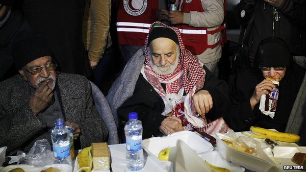 Evacuated residents from a besieged area of Homs eat after their arrival to the area under government control February 7, 2014