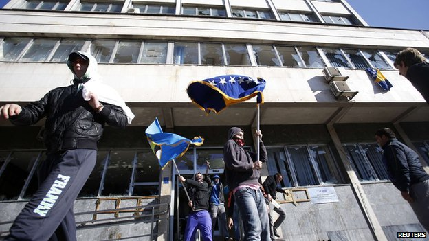 Protesters walk out of a damaged government building in Tuzla February 7, 2014.